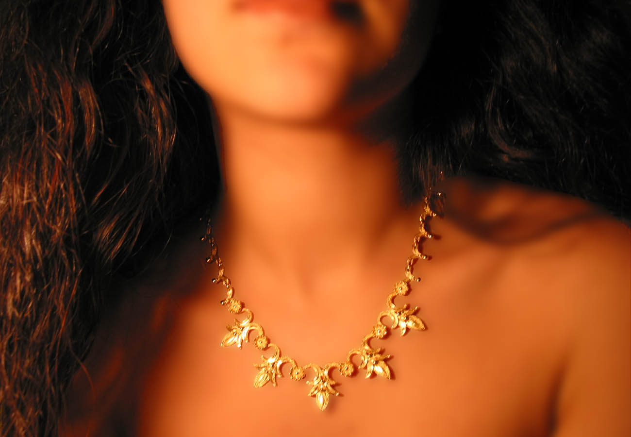 18k gold necklace with repeated motifs of interconnected lotus and rosette leaves