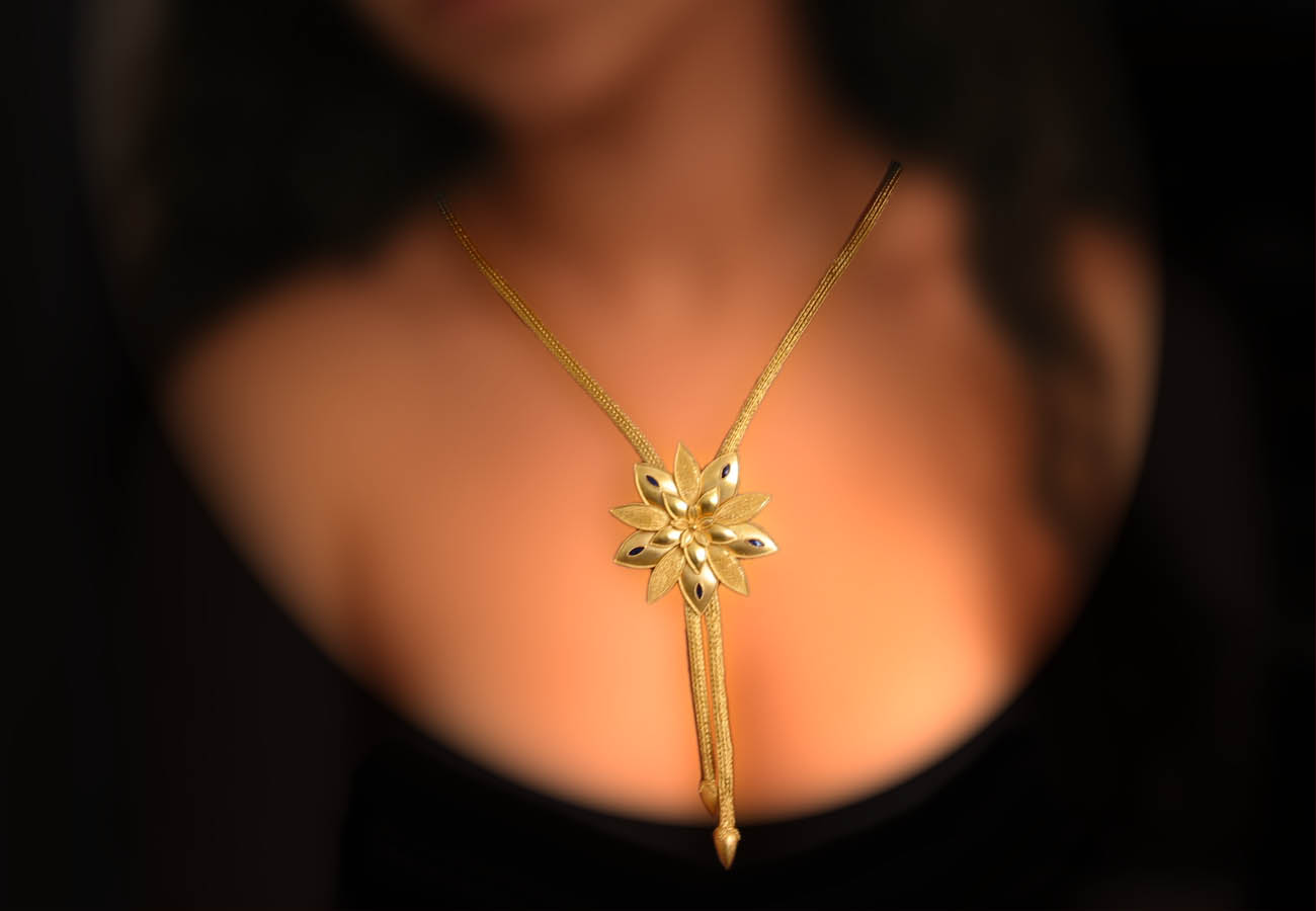 22k gold chain necklace, the element in the shape of lily is hanging in the middle, decorated with enamel