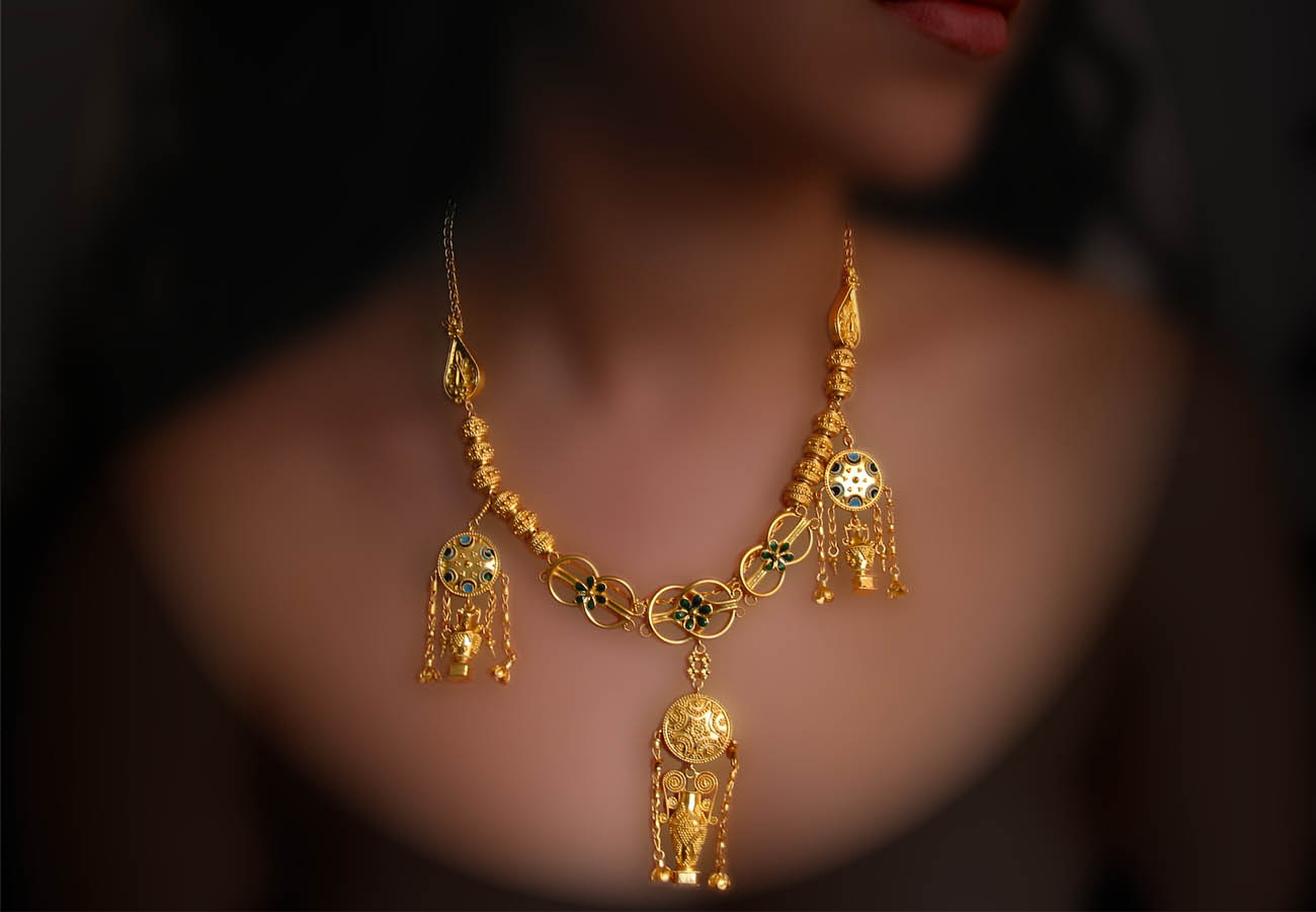 22k gold elements in the shape of vase which are hanging from discs placed in a necklace