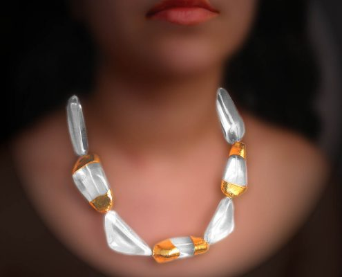 22k yellow gold necklace and a variety of gemstone shapes from a semi-precious stone