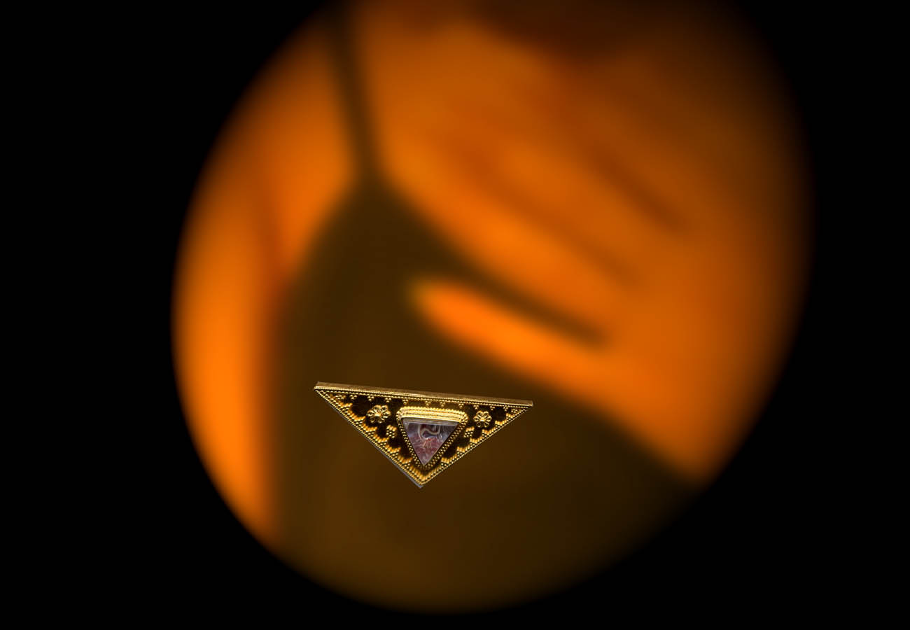 22k yellow gold triangular shape brooch embellished with tiny specks of gold and a semi-precious stone