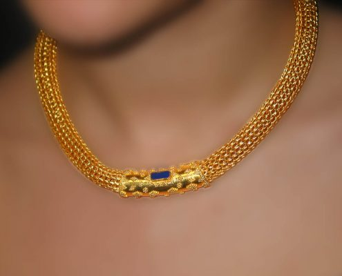 18k gold chain necklace with speckled decoration and a semi-precious stone as the central attraction
