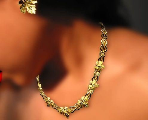 18k gold creation with repeated motifs of the knot of Heraklion and grapevine leaves embellished with diamonds