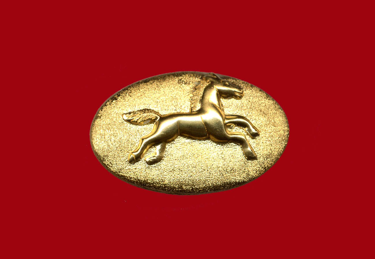 22k gold brooch in an oval shape with a running horse in the middle
